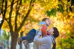 Ευτυχής νέα μητέρα που κρατά το γλυκό αγόρι μικρών παιδιών, οικογένεια που έχει τη διασκέδαση στοκ εικόνες