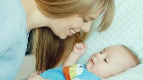 Ευτυχής νέα μητέρα που χαμογελά στο γιο του δύο μήνες Το μωρό βρίσκεται στο παχνί φιλμ μικρού μήκους