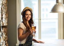 Ευτυχής νέα μπύρα κατανάλωσης γυναικών στο φραγμό ή το μπαρ Στοκ εικόνες με δικαίωμα ελεύθερης χρήσης
