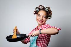 Ευτυχής νέα νοικοκυρά με ένα τηγανίζοντας τηγάνι σε ένα γκρίζο υπόβαθρο Στοκ εικόνες με δικαίωμα ελεύθερης χρήσης
