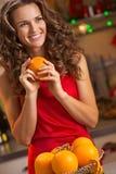 Ευτυχής νέα νοικοκυρά με τα πορτοκάλια στην κουζίνα Χριστουγέννων Στοκ Εικόνα