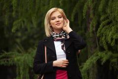 Ευτυχής νέα ξανθή γυναίκα μόδας που περπατά στο πάρκο πόλεων στοκ φωτογραφία