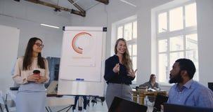 Ευτυχής νέα ξανθή οικονομική γυναίκα επιχειρησιακών λεωφορείων που διδάσκει τη multiethnic ομάδα εργαζομένων στο σύγχρονο σεμινάρ απόθεμα βίντεο