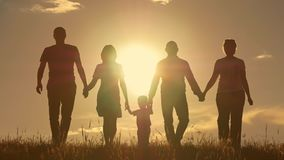 Ευτυχής νέα οικογένεια με τα παιδιά που τρέχουν γύρω από τον τομέα, σκιαγραφία στο ηλιοβασίλεμα Στοκ φωτογραφία με δικαίωμα ελεύθερης χρήσης