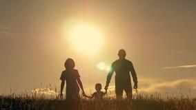 Ευτυχής νέα οικογένεια με τα παιδιά που τρέχουν γύρω από τον τομέα, σκιαγραφία στο ηλιοβασίλεμα Στοκ εικόνες με δικαίωμα ελεύθερης χρήσης