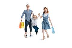 Ευτυχής νέα οικογένεια με τις τσάντες μιας παιδιών αγορών εκμετάλλευσης στοκ εικόνες