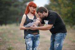 Ευτυχής νέα οικογένεια με το νεογέννητο μωρό στον περίπατο στο πάρκο στοκ εικόνα