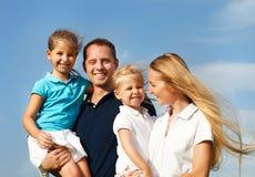 Ευτυχής νέα οικογένεια με δύο παιδιά υπαίθρια Στοκ Εικόνα