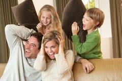 Ευτυχής νέα οικογένεια που έχει τη διασκέδαση με τα μαξιλάρια στον καναπέ Στοκ Εικόνες