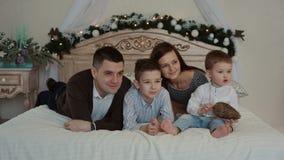 Ευτυχής νέα οικογένεια που βρίσκεται στο κρεβάτι φιλμ μικρού μήκους
