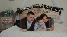 Ευτυχής νέα οικογένεια που βρίσκεται στο κρεβάτι απόθεμα βίντεο