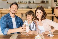 ευτυχής νέα οικογένεια που πίνει milkshakes στον καφέ και τα έξοδα στοκ εικόνες