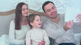 Ευτυχής νέα οικογένεια που παίρνει selfies στον καναπέ με την ταμπλέτα φιλμ μικρού μήκους