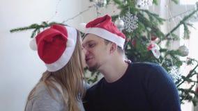 Ευτυχής νέα οικογένεια σε Santa ΚΑΠ Ο σύζυγος τον φιλά έγκυος σύζυγος κοντά στο όμορφο διακοσμημένο χριστουγεννιάτικο δέντρο κίνη απόθεμα βίντεο