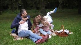 Ευτυχής νέα οικογένεια στο παιχνίδι πάρκων φθινοπώρου με τα παιδιά Μπαμπάς, mom, γιος, κόρη Παιδιά που οργανώνονται στους γονείς  απόθεμα βίντεο