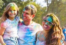 Ευτυχής νέα οικογένεια στο φεστιβάλ χρώματος holi Στοκ Εικόνες