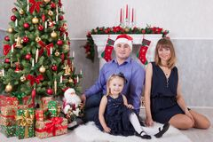 Ευτυχής νέα οικογένεια στο χριστουγεννιάτικο δέντρο με μια εστία Στοκ φωτογραφίες με δικαίωμα ελεύθερης χρήσης