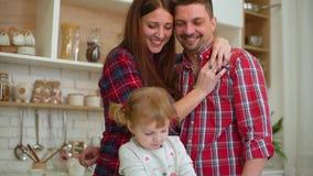 Ευτυχής νέα οικογένεια τριών που έχουν τη διασκέδαση μαζί στην κουζίνα απόθεμα βίντεο