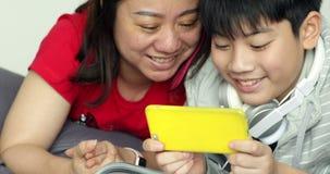 Ευτυχής νέα προσοχή μητέρων και γιων στο κύτταρο Κατόπιν αυτοί που κοιτάζουν μέσω του τηλεφώνου με το πρόσωπο χαμόγελου απόθεμα βίντεο