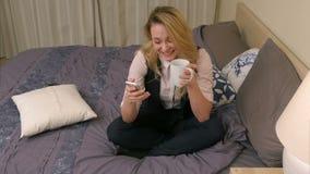 Ευτυχής νέα συνεδρίαση γυναικών στο κρεβάτι, αστείο μήνυμα ανάγνωσης στο τσάι smartphone, χαμόγελου και κατανάλωσης απόθεμα βίντεο