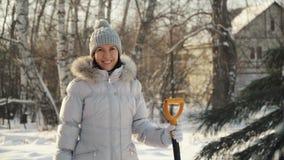Ευτυχής νέα τοποθέτηση γυναικών στη κάμερα με το φτυάρι στα προάστια το χειμώνα απόθεμα βίντεο