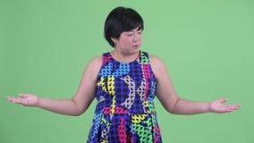 Ευτυχής νέα υπέρβαρη ασιατική γυναίκα που συγκρίνει κάτι έτοιμο με το κόμμα φιλμ μικρού μήκους