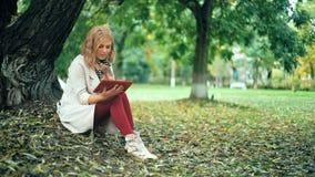 Ευτυχής νέα χαλάρωση γυναικών στο πάρκο φθινοπώρου με την ταμπλέτα Κίτρινα δέντρα, όμορφος χρόνος πτώσης απόθεμα βίντεο