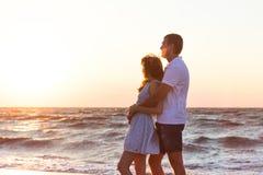 Ευτυχής νέα χαλάρωση ζευγών στην παραλία στο ηλιοβασίλεμα διακοπές ονείρου Στοκ Φωτογραφίες