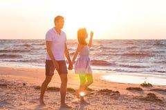 Ευτυχής νέα χαλάρωση ζευγών στην παραλία στο ηλιοβασίλεμα διακοπές ονείρου Στοκ Εικόνες