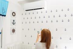 Ευτυχής νέα χαλάρωση τηλεχειρισμού εκμετάλλευσης γυναικών κάτω από το κλιματιστικό μηχάνημα στοκ εικόνα