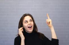 Ευτυχής νέα χαμογελώντας γυναίκα που μιλά στο τηλέφωνο και που δείχνει ένα δάχτυλο στο διάστημα αντιγράφων στοκ εικόνα με δικαίωμα ελεύθερης χρήσης