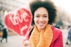 Ευτυχής νέα χαμογελώντας γυναίκα με τη μεγάλη κόκκινη καρδιά στην ηλιόλουστη ημέρα Στοκ φωτογραφία με δικαίωμα ελεύθερης χρήσης