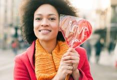 Ευτυχής νέα χαμογελώντας γυναίκα με τη μεγάλη κόκκινη καρδιά στην ηλιόλουστη ημέρα Στοκ Εικόνα