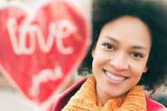 Ευτυχής νέα χαμογελώντας γυναίκα με τη μεγάλη κόκκινη καρδιά στην ηλιόλουστη ημέρα Στοκ εικόνα με δικαίωμα ελεύθερης χρήσης