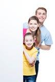Ευτυχής νέα χαμογελώντας οικογένεια με το έμβλημα Στοκ εικόνα με δικαίωμα ελεύθερης χρήσης