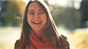 Ευτυχής νέα όμορφη γυναίκα που γελά και που κοιτάζει στη κάμερα, υπόβαθρο πάρκων πτώσης Πρώιμο φθινόπωρο τον Οκτώβριο απόθεμα βίντεο