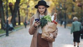 Ευτυχής νέα όμορφη γυναίκα που φορά το μοντέρνο παλτό που περπατά στη συσκευασία εκμετάλλευσης πάρκων των προϊόντων και που χρησι φιλμ μικρού μήκους