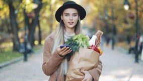 Ευτυχής νέα όμορφη γυναίκα που φορά το μοντέρνο παλτό που περπατά στη συσκευασία εκμετάλλευσης πάρκων των προϊόντων και που χρησι απόθεμα βίντεο