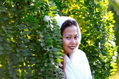 Ευτυχής νέα όμορφη γυναίκα στο πάρκο φθινοπώρου την ηλιόλουστη ημέρα, νέα γυναίκα στο άσπρο παλτό κατά τη διάρκεια του ηλιοβασιλέ Στοκ φωτογραφία με δικαίωμα ελεύθερης χρήσης