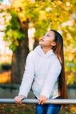 Ευτυχής νέα όμορφη γυναίκα στο πάρκο φθινοπώρου την ηλιόλουστη ημέρα, νέα γυναίκα στο άσπρο παλτό κατά τη διάρκεια του ηλιοβασιλέ Στοκ εικόνες με δικαίωμα ελεύθερης χρήσης