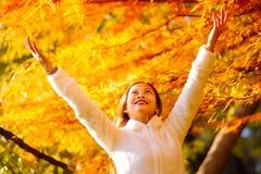 Ευτυχής νέα όμορφη γυναίκα στο πάρκο φθινοπώρου την ηλιόλουστη ημέρα, νέα γυναίκα στο άσπρο παλτό κατά τη διάρκεια του ηλιοβασιλέ Στοκ εικόνα με δικαίωμα ελεύθερης χρήσης