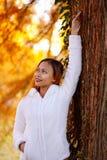 Ευτυχής νέα όμορφη γυναίκα στο πάρκο φθινοπώρου την ηλιόλουστη ημέρα, νέα γυναίκα στο άσπρο παλτό κατά τη διάρκεια του ηλιοβασιλέ Στοκ Φωτογραφίες