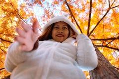 Ευτυχής νέα όμορφη γυναίκα στο πάρκο φθινοπώρου την ηλιόλουστη ημέρα, νέα γυναίκα στο άσπρο παλτό κατά τη διάρκεια του ηλιοβασιλέ Στοκ Εικόνα