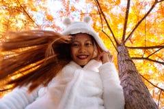Ευτυχής νέα όμορφη γυναίκα στο πάρκο φθινοπώρου την ηλιόλουστη ημέρα, νέα γυναίκα στο άσπρο παλτό κατά τη διάρκεια του ηλιοβασιλέ Στοκ Φωτογραφία