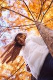 Ευτυχής νέα όμορφη γυναίκα στο πάρκο φθινοπώρου την ηλιόλουστη ημέρα, νέα γυναίκα στο άσπρο παλτό κατά τη διάρκεια του ηλιοβασιλέ Στοκ Εικόνες