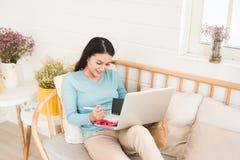 Ευτυχής νέος ασιατικός επιχειρηματίας που εργάζεται με ένα lap-top στο σπίτι Στοκ Εικόνα