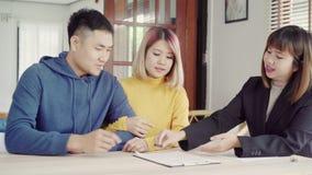Ευτυχής νέος ασιατικός πράκτορας ζευγών και realtor Εύθυμος νεαρός άνδρας που υπογράφει μερικά έγγραφα καθμένος στο γραφείο μαζί  απόθεμα βίντεο