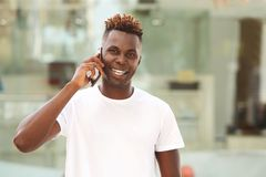 Ευτυχής νέος αφρικανικός τύπος ατόμων που κάνει ένα τηλεφώνημα και ένα χαμόγελο Στοκ φωτογραφία με δικαίωμα ελεύθερης χρήσης