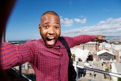 Ευτυχής νέος αφρικανικός τύπος που δείχνει στην πόλη Στοκ Φωτογραφία