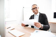 Ευτυχής νέος επιχειρηματίας που εργάζεται με τα έγγραφα στην αρχή Στοκ Φωτογραφία